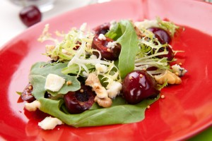 Green salad with sweet cherries, candied pistachios and goat cheese rounds